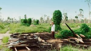 In Kambodscha steht ein vom Landraub Betroffener auf den Trümmern seines zerstörten Hauses. © dpa/Movienet